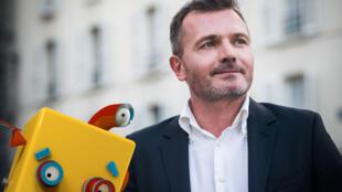 Benoît Raphaël avec une représentation physique de son robot virtuel Flint.
