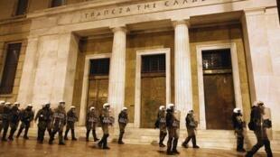 Policías protegen el edificio del Banco de Grecia durante una manifestación contra el plan de austeridad, en el centro de Atenas, el 19 de febrero de 2012.