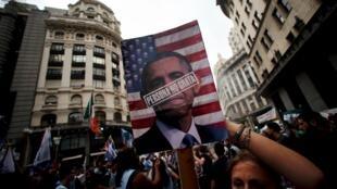 """Una mujer sostiene un cartel que dice """"persona non carta"""" con el rostro del presidente de EEUU durante una manifestación conmemorativa del 40 aniverseario del golpe de estado de 1976. El 24 de marzo de 2016 en Buenos Aires."""