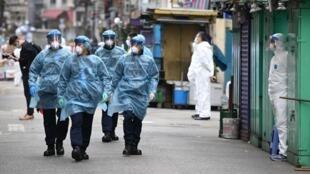 警察穿着防护服于2021年1月24日在香港部分受限的乔丹街区巡逻。La policía, usando trajes de protección, patrulla las calles del vecindario Jordan, parcialmente confinado, en Hong Kong, el 24 de enero de 2021