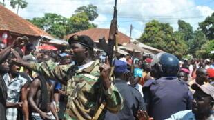 Les forces de l'ordre essayent de protéger un Nigérian accusé par la foule de rapt d'enfant, à Bissau, le 8 octobre 2013.