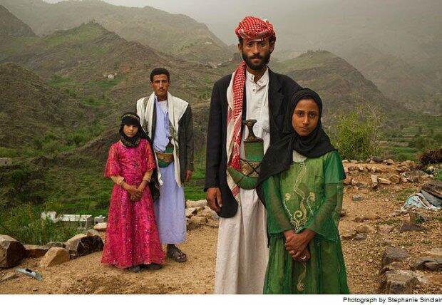 Dois homens posam ao lado de suas esposas, meninas entre 10 e 12 anos