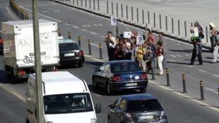 Grupo de pessoas protesta diante do Ministério das Finanças, em Lisboa, enquanto o ministro Vítor Gaspar anunciava as novas medidas de austeridade para 2013, nesta quarta-feira.