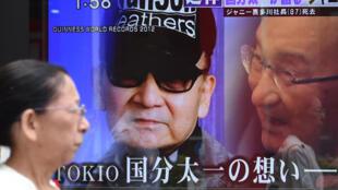 Une femme passe devant un écran de télévision annonçant la mort de Johnny Kitagawa, fondateur tout-puissant de Johnny & Associates, à Tokyo, le 9 juillet 2019.