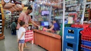 Em Buenos Aires, caixa de supermercado trabalha protegida por uma cortina de plástico para evitar contato com possíveis portadores do coronavírus.