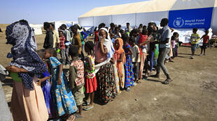 Ethiopian refugees who have fled the Tigray conflict queue for food outside UNHCR and World Food Programme tents at Sudan's Hamdayit transit centre on November 27, 2020