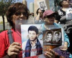 Lebanese women hold pictures of their relatives missing since the Lebanese civil war