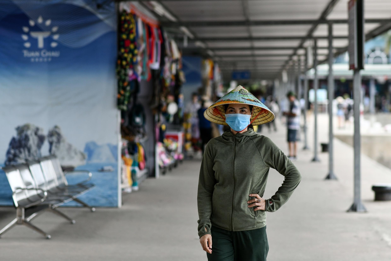 A woman wearing a face mask walks along the Tuan Chau harbour in Ha Long Bay, Vietnam
