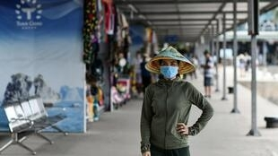 A woman wearing a face mask walks along the Tuan Chau harbour in Ha Long Bay, Vietnam