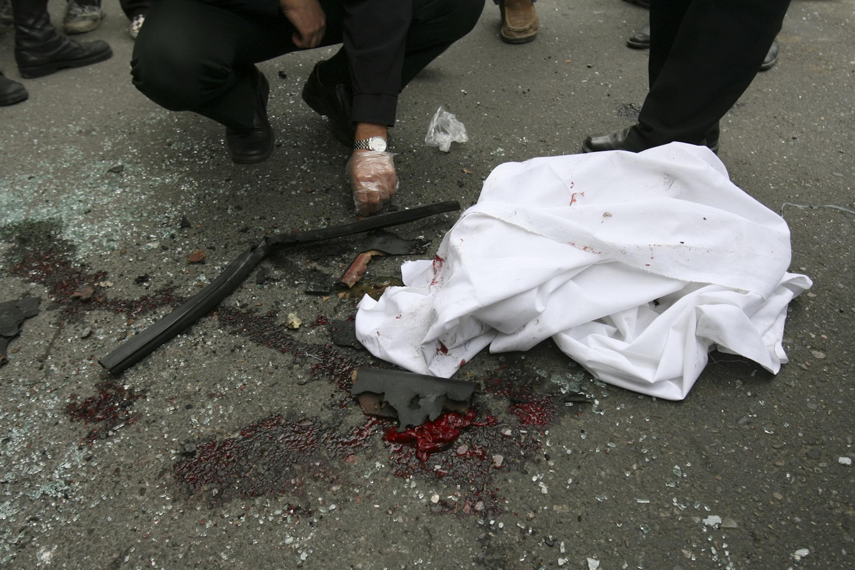 Policiail iraniano verifica os restos do carro que pertencia ao cientista Mostafa Ahmadi-Roshan, assassinado nesta quarta-feira por um atentado à bomba no norte de Teerã.
