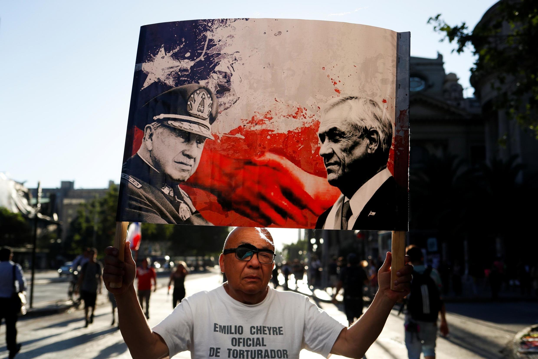 Un homme tient une pancarte représentant le président chilien Sebastian Pinera et le défunt dictateur Augusto Pinochet lors d'une manifestation contre le gouvernement chilien à Santiago du Chili, le 15 novembre 2019.
