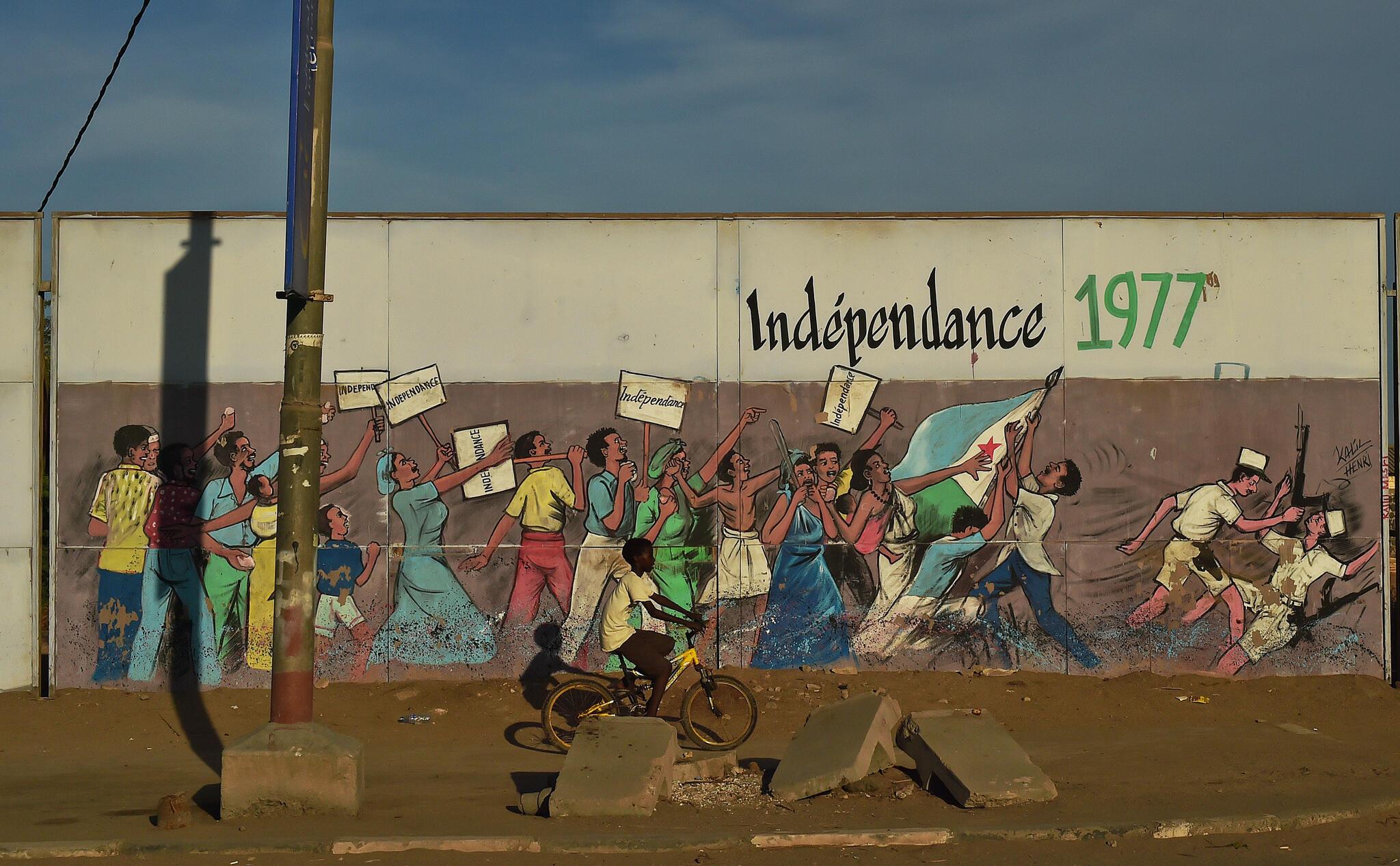 Un enfant passe à vélo devant une fresque qui dépeint l'indépendance du Djibouti en 1977.
