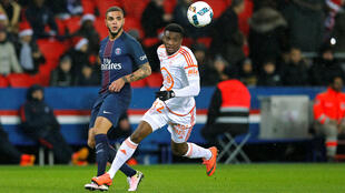 Benjamin Moukandjo (right) fights for the ball against Paris Saint-Germain's Layvin Kurzawa. Moukandjo will leave Lorient for up to a month to skipper Cameroon at the Africa Cup of Nations.