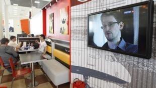 Edward Snowden à la télévision, lors d'un bulletin d'informations, dans un café de l'aéroport Sheremetyevo, à Moscou, le 26 juin 2013.