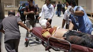 Des secouristes évacuent un blessé vers l'hôpital de Bagdad après l'attentat qui a secoué cette ville ce 4 juin 2012.
