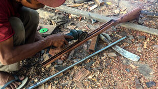 A member of a local 'defence force' makes a handmade gun to be used against security forces in Myanmar's Kayah state
