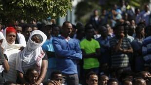 Em Lampedusa, imigrantes clandestinos observam um memorial em homenagem às vítimas de naufrágios.