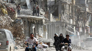 ស្រ្តីៗនាំគ្នាដើរកាត់ថ្មីបាក់បែកនៃអគារនៅក្រុង Raqqa ប្រទេស ស៊ិរី ថ្ងៃទី១៤ ឧសភាឆ្នាំ២០១៨ REUTERS/Aboud Hamam
