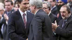 Le Premier ministre canadien Stephen Harper (de dos) serre la main de l'un des leaders de l'opposition, Justin Trudeau, sous les applaudissements de la Chambre des communes pour son retour au travail, jeudi 23 octobre 2014.