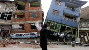 Un homme marche à côté des immeubles éffondrés, secoués par un tremblement de terre à  Ercis, dans l'est de la Turquie, le 29 octobre 2011.