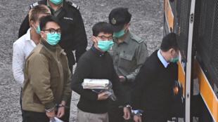 Los activistas prodemocracia de Hong Kong Joshua Wong (centro) e Ivan Lam (izq) antes de subir a un vehículo policial para ser conducidos ante un tribunal, en Hong Kong el 2 de diciembre de 2020