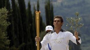 Spyridon Gianniotis, nadador grego campeão do mundo, corre com a chama olímpica, após encenação nas ruínas milenares de Olímpia, nesta quinta-feira.