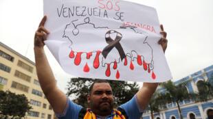 Un manifestant tient une pancarte portant l'inscription «SOS Le Venezuela saigne» lors d'une manifestation contre le gouvernement du président vénézuélien Nicolas Maduro, en marge d'une rencontre diplomatique à Lima, au Pérou 8 août.