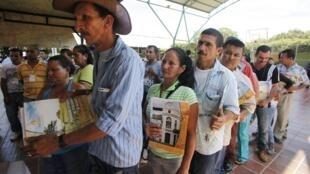 Campesinos colombianos desplazados por la guerra interna hacen cola para recibir títulos de granjas vacantes como compensación de la administración de Santos.