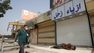 Un Irakien portant un masque facial et des gants passe devant un sans-abri qui dort devant un magasin fermé pendant un couvre-feu imposé à Bassora, le 2 avril 2020.