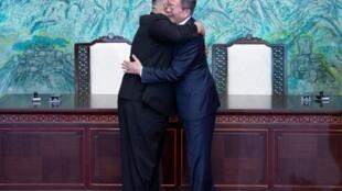 Os dirigentes coreanos Kim Jong-un (esquerda) e Moon Jae-in se abraçam após divulgar um compromisso histórico de busca da paz e da desnuclearização da península.