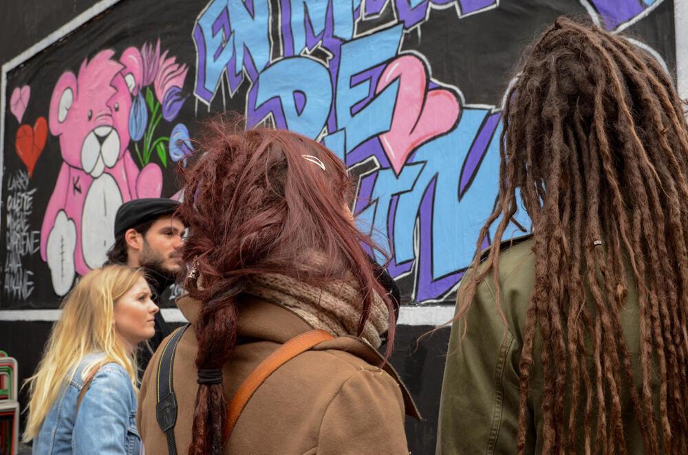 The tour begins at the Café Place Verte on the rue Oberkampf, beside a mural by street artist Sheedak