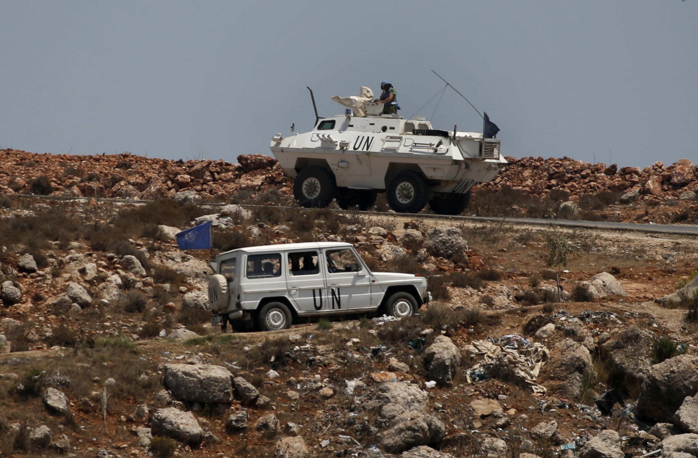Dos vehículos de la Fuerza Interina de Naciones Unidas en Líbano (UNIFIL) circulan por las proximidades del pueblo libanés de Kfar Kila mientras patrullan la frontera israelí, una imagen tomada el 5 de agosto de 2021 desde Metula, al norte de Israel