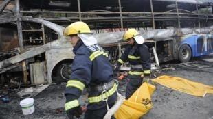 Lính cứu hỏa thu lượm xác các nạn nhân vụ tai nạn tại Diên An, Thiểm Tây ngày 26/08/2012.