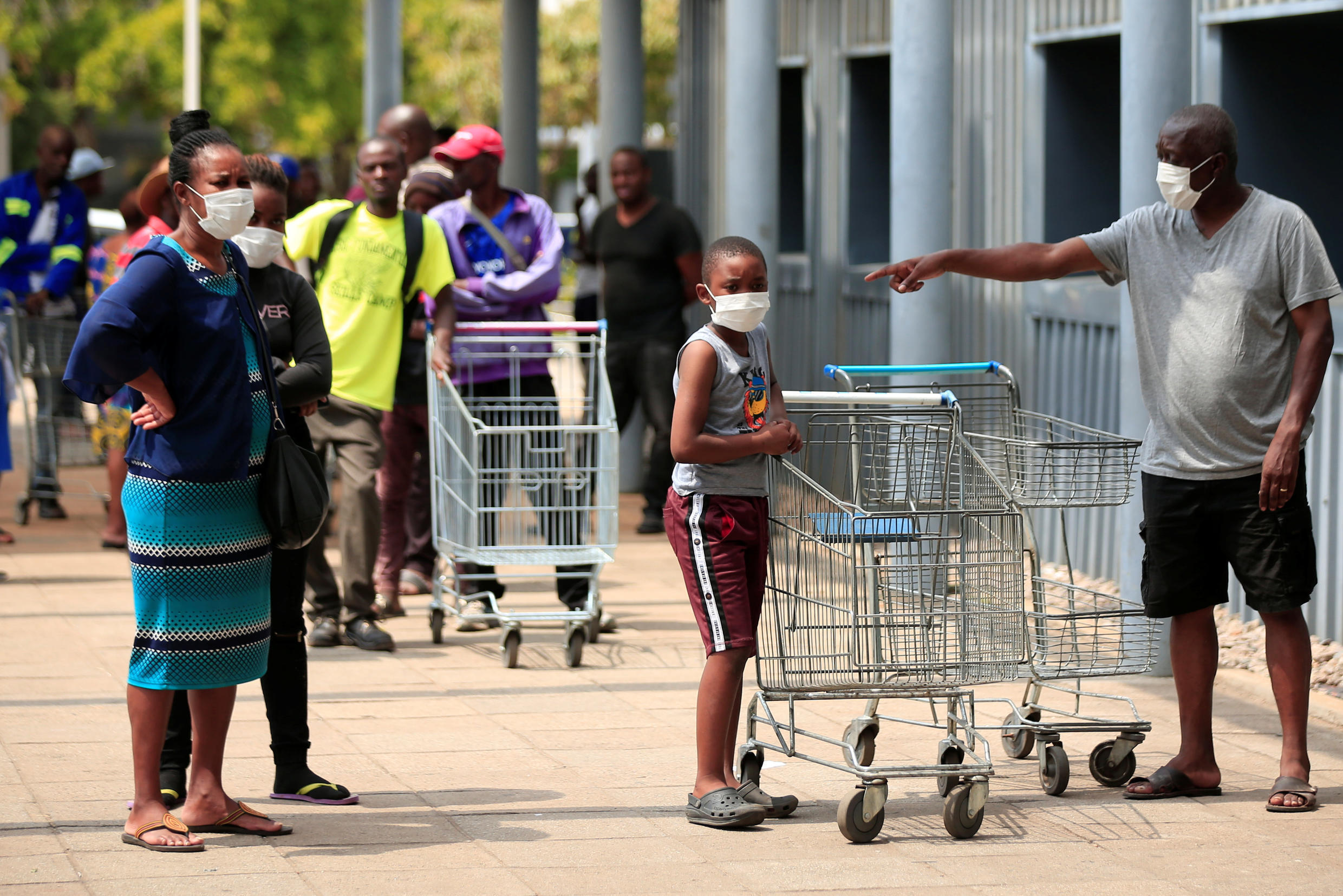 People queue to shop ahead of a nationwide 21-day lockdown called by the government to limit the spread of coronavirus disease (COVID-19) in Harare, Zimbabwe, March 28, 2020.