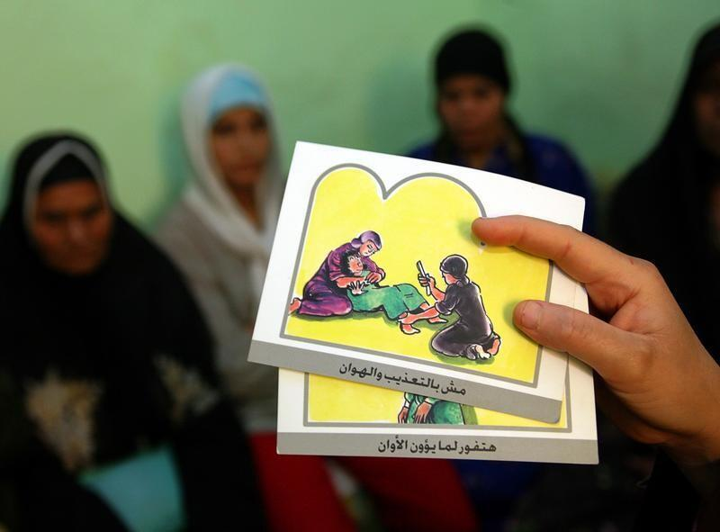 A counsellor holds up cards used to educate women about female genital mutilation (FGM) in Minia, Egypt, June 13, 2006.