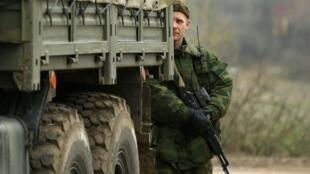 Militar armado, supostamente russo, faz a guarda da base militar perto da cidade de Sebastopol, na Crimeia, nesta sexta-feira (7).