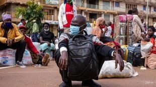 Un voyageur porte un masque à titre préventif contre la propagation du coronavirus COVID-19, alors qu'il attend un bus interurbain au Namirembe Bus Park à Kampala, en Ouganda, le 4 juin 2020, premier jour de ouverture des transports publics.
