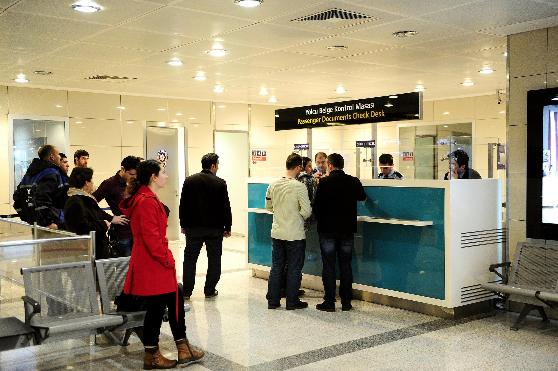 La police contrôle les passeports de passagers à un poste de douane de l'aéroport international d'Istanbul.