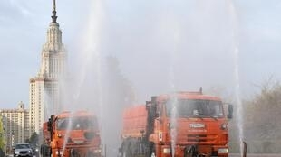 Vehicles spray disinfectant while sanitizing a road near the main building of the Lomonosov Moscow State University amid the coronavirus disease (COVID-19) outbreak in Moscow, Russia April 24, 2020.