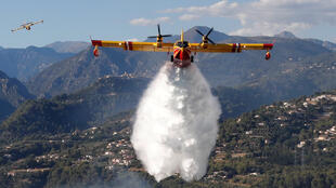 A Canadair firefighting aircraft drops water on a wildfire which burns a forest in Carros, near Nice, France, July 24, 2017.