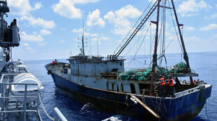 Tầu chiến Indonesia KRI Imam Bonjol (T) kiểm soát một tầu đánh cá Trung Quốc trong vùng biển gần quần đảo Natuna của Indonesia.