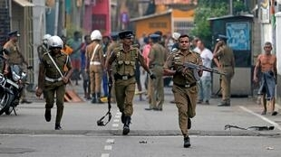 Des policiers sri-lankais évacuent le site d'une explosion près d'une église attaquée dimanche (21 avril 2019) où enquêtent les forces de déminage, le 22 avril 2019.