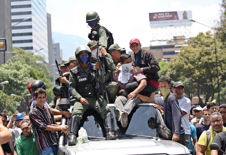 Des soldats rejoignent des partisans du leader de l'opposition vénézuélienne Juan Guaido sur le toit d'une voiture lors des manifestations anti-gouvernementales à Caracas, le 30 avril 2019.