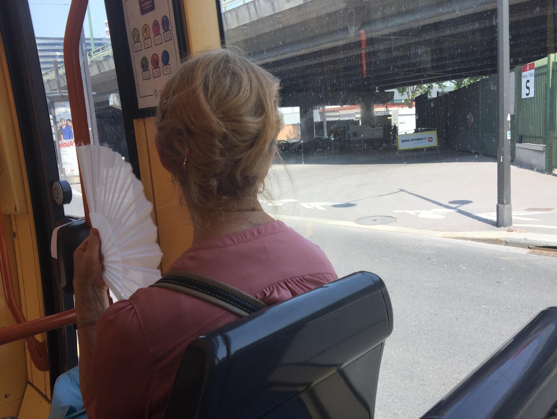 Senhora com leque branco em transporte público em dia de 37° à sombra