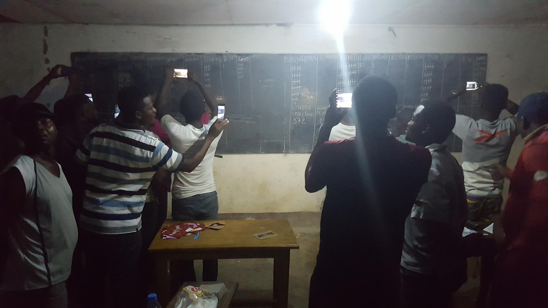 Les electeurs qui ont assisté au depouillement prennent des photos et filment le tableau où sont inscrits les résultats dans un bureau de vote de Douala.