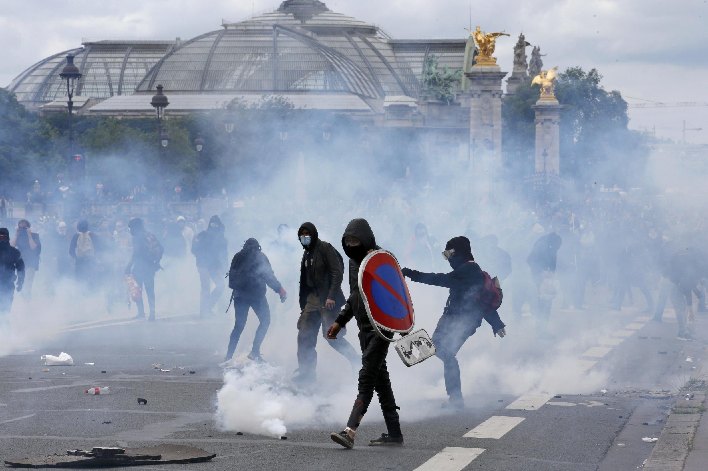 Masked youths face French police on 14 June demonstration against the labour reform
