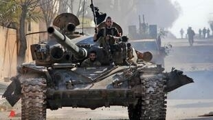 Syrian fighters supported by Turkey drive a tank through the town of Saraqib, in eastern Idlib province, 27 February 2020