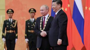 Presidente chinês, Xi Jinping, condecora Presidente russo, Putin, no primeiro dia da sua visita à China