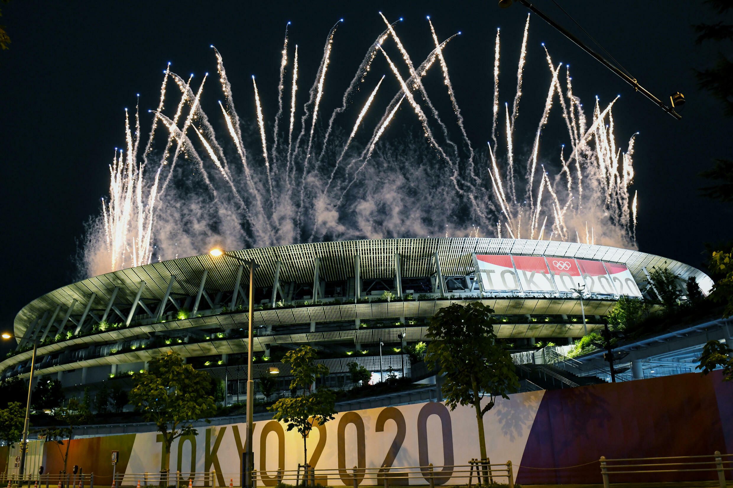 Virus rules kept fans out of the Olympic opening ceremony but many gathered nearby to watch