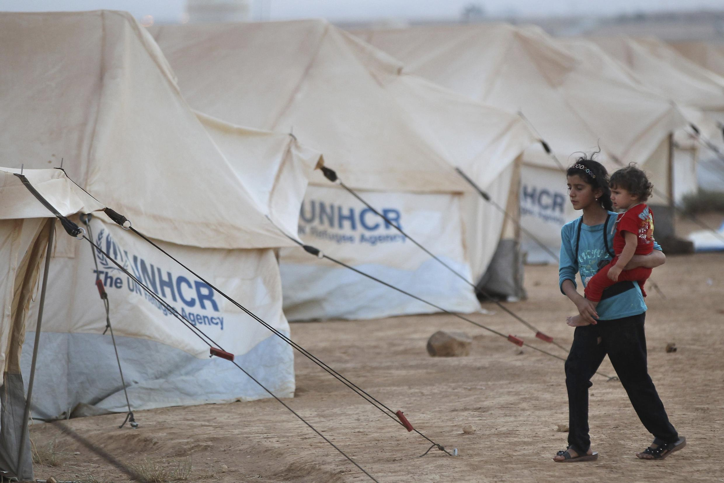 A Syrian girl carries her brother at the Al Zaatri refugee camp in the Jordanian city of Mafraq, 31 July, 2012